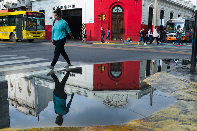 A girl walk by a puddle after a storm in Rosario