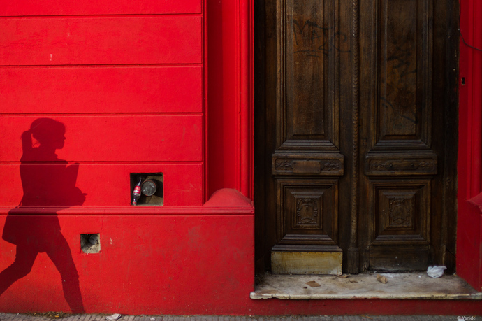 A girl shadows can be seen on a red wall in Rosario